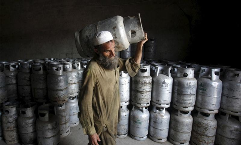 A man carries an LPG cylinder at a gas distribution centre in Peshawar. — Reuters/File