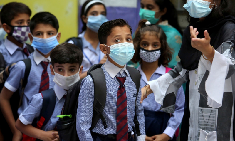 Students wearing face masks to prevent the spread of the coronavirus arrive at a primary school in this file photo. — AFP