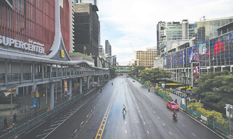 A MAN crosses the road on an intersection after the strict lockdown restrictions took effect.—AFP
