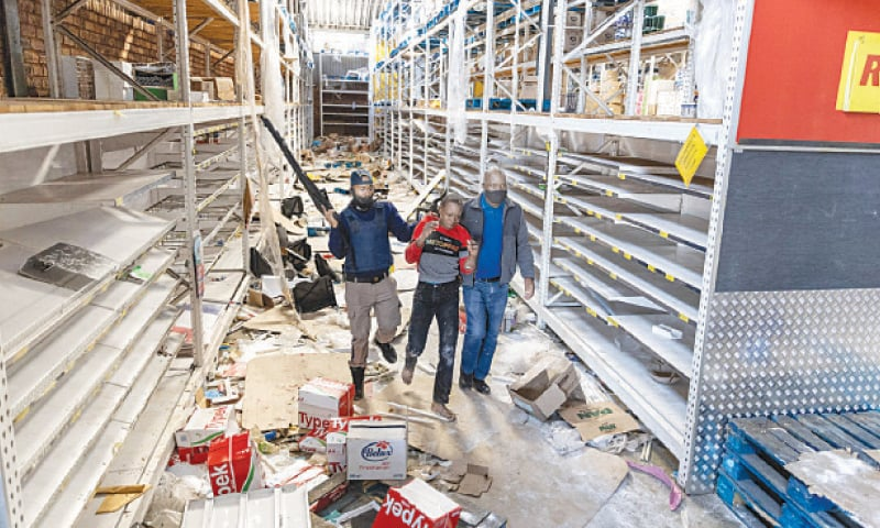 POLICE arrest a looter at a shopping centre in Vosloorus, near Johannesburg.—AFP