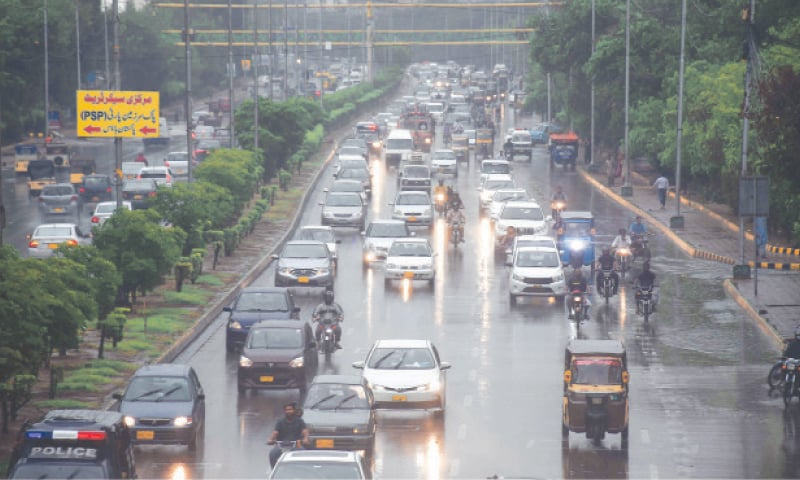 Monday morning's rainfall is seen in this Online photo and (right) vehicles navigate a flooded road at Qayyumabad (Shakil Adil/White Star).