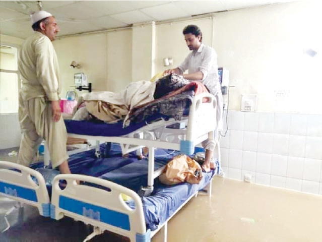 Attendants take care of a patient in a flooded ward of Ayub Medical Complex. — Dawn