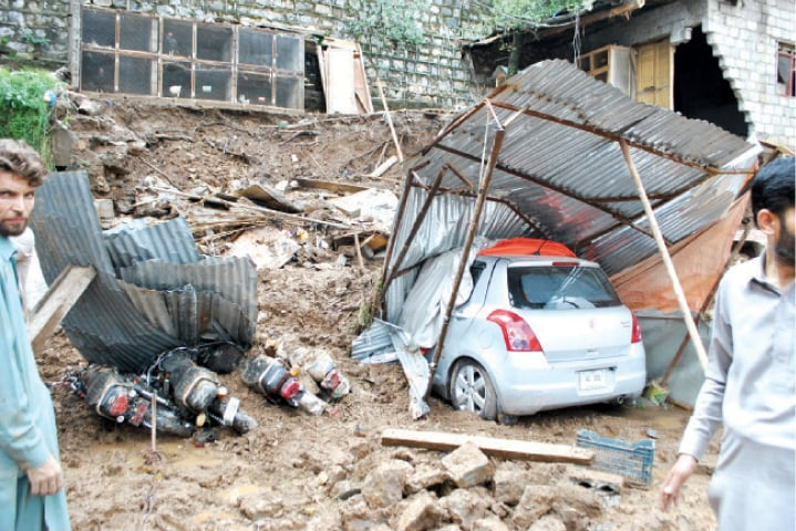 A car and motorcycles buried in debris after a wall collapsed due to heavy rain in Abbottabad on Monday. — Dawn