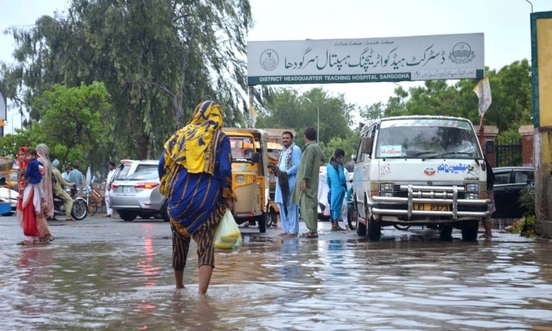 People wade through water after heavy rain in front of DHQ Hospital in Sargodha. — APP