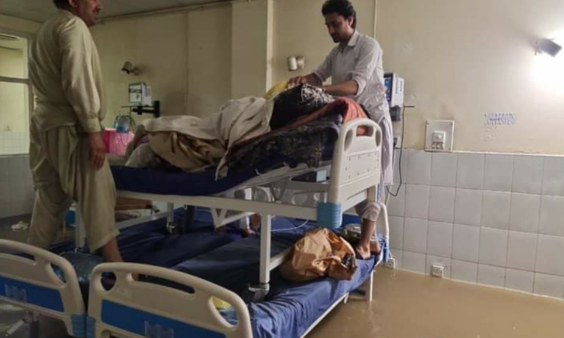 People stack a hospitall bed on top of two other beds as water fills up the Ayub Medical Complex in Abbottabad. — Photo by Sirajuddin