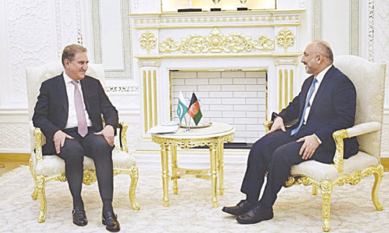 DUSHANBE: Foreign Minister Shah Mahmood Qureshi speaks to his Afghan counterpart Mohammad Hanif Atmar during a meeting held on the sidelines of SCO Council of Foreign Ministers on Tuesday.—APP