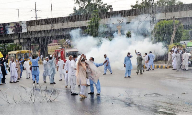 Smoke rises in the background as the police fired tear gas shells on government officers protesting near the provincial assembly's building in Peshawar on Tuesday. — White Star