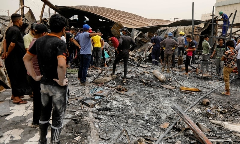 People gather as they inspect the damage at al-Hussain coronavirus hospital where a fire broke out, in Nassiriya, Iraq, July 13. — Reuters