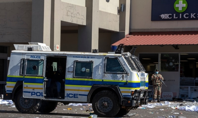 Soldiers patrol and police at a shopping centre in Soweto on July 13. — AP