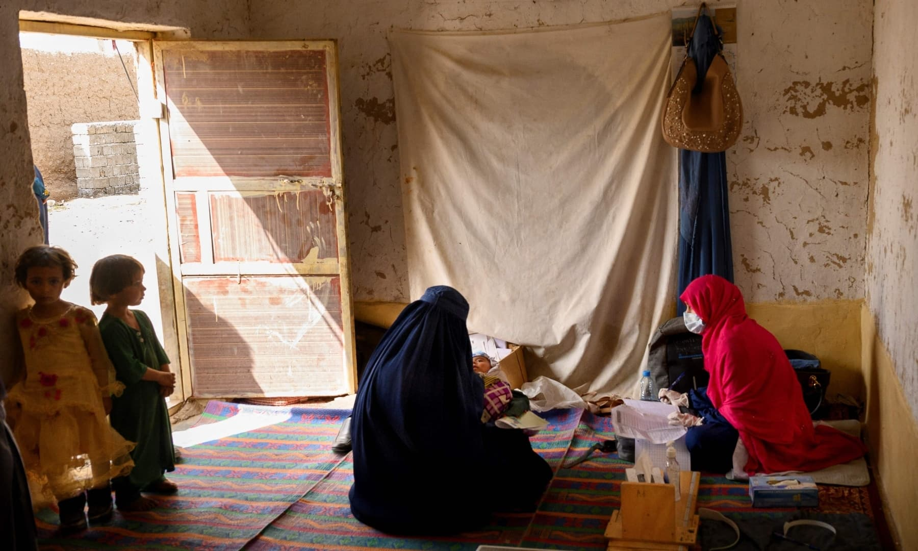 A nurse (R) registers a patient at a mobile clinic set up at the residence of a local elder in Yarmuhamad village, near Lashkar Gah in Helmand province, Afghanistan, March 28, 2021. — AFP/File