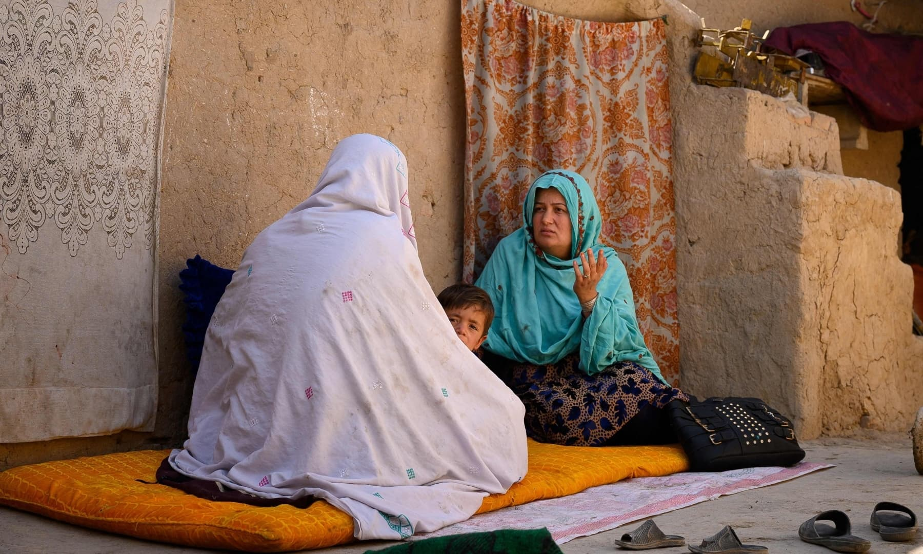 A midwife (R) speaks to a woman during a house visitation in a rural area of Dand district in Kandahar province, Afghanistan, October 1, 2020. — AFP/File