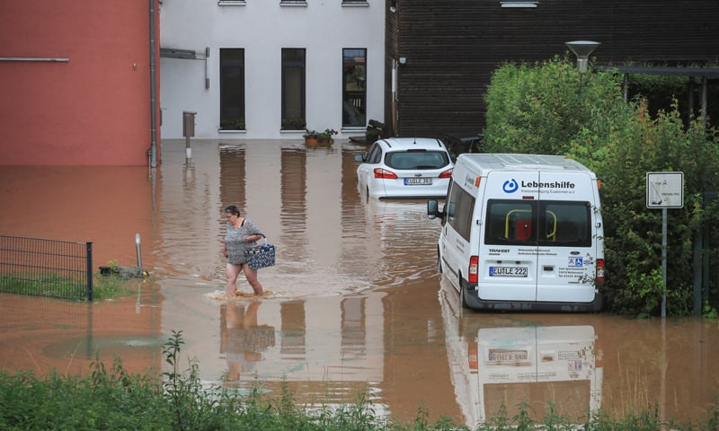 A woman wades across floodwater as she goes out shopping following heavy rainfalls in Gross-Vernich, Germany. — Reuters