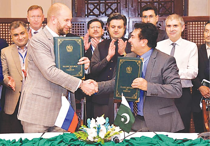 ISLAMABAD: Department of Foreign Economic Cooperation and Fuel Markets Development Deputy Director Alexander Tolparov and Petroleum Division Secretary Dr Arshad Mahmood shake hand after signing an MoU on Thursday. Energy Minister Hammad Azhar looks on.—White Star