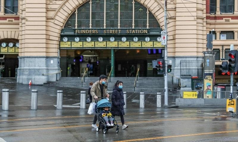 People wearing mask walk past the Flinders Street station in Melbourne on July 16. — AFP