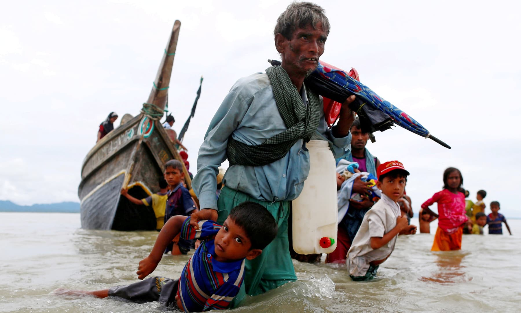 A Rohingya refugee man pulls a child as they walk to the shore after crossing the Bangladesh-Myanmar border by boat through the Bay of Bengal in Shah Porir Dwip, Bangladesh, September 10, 2017. — Reuters/Danish Siddiqui
