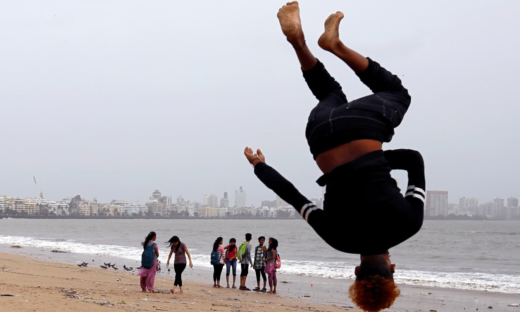 Beachgoers stroll as a boy practices somersaulting on a beach in Mumbai, India, July 12, 2018. — Reuters/Danish Siddiqui