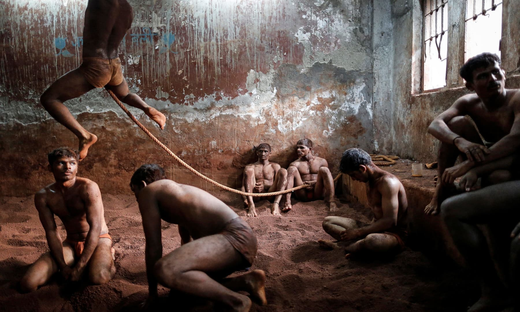 Wrestlers practise as others rest in the mud at a traditional Indian wrestling centre called Akhaara in Mumbai, March 4, 2014. — Reuters/Danish Siddiqui