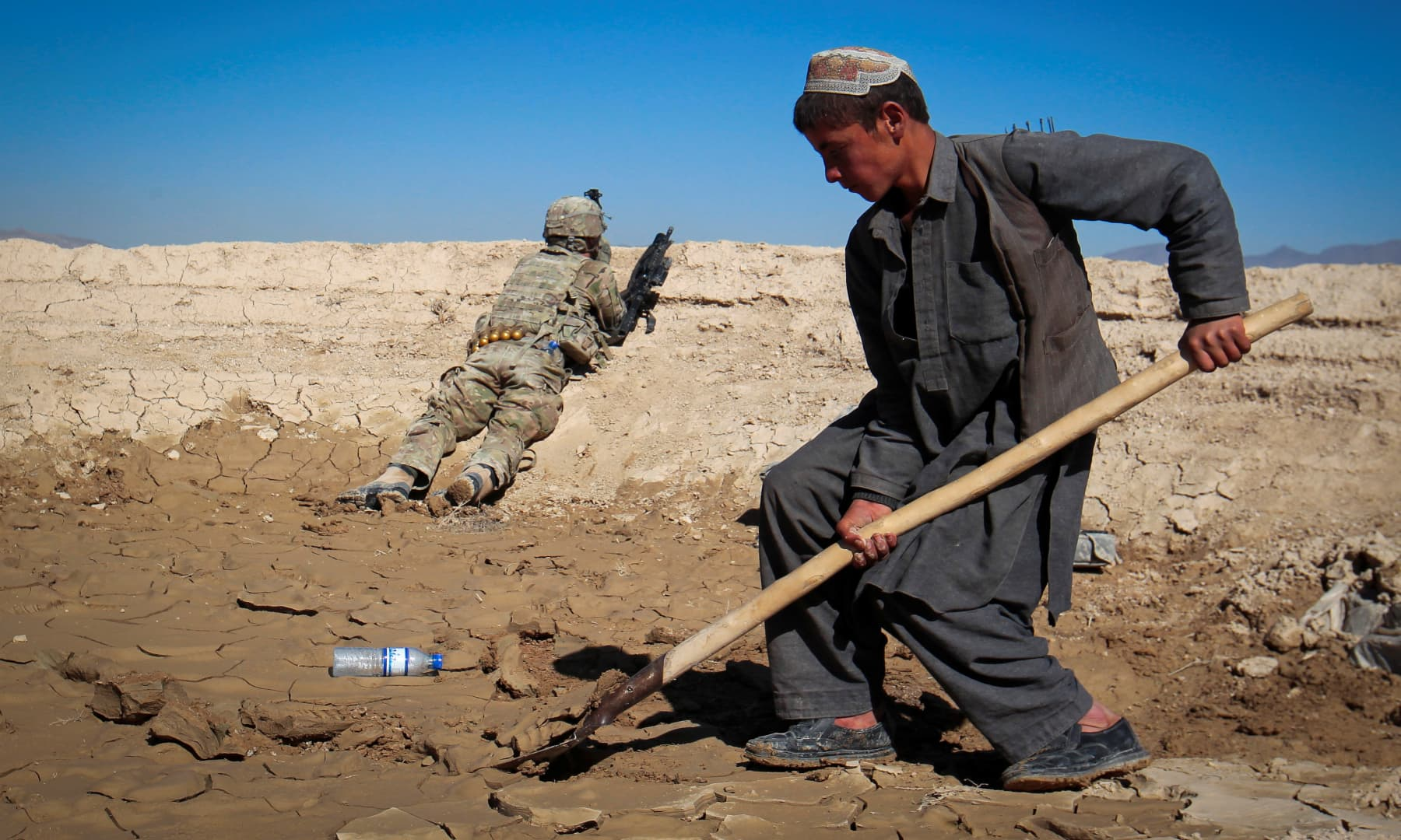 An Afghan boy works at a construction site as a US Army soldier of 3/1 AD Task Force Bulldog takes position during a joint patrol with Afghan National Army in a village in Kherwar district in Logar province, eastern Afghanistan, May 23, 2012. — Reuters/Danish Siddiqui