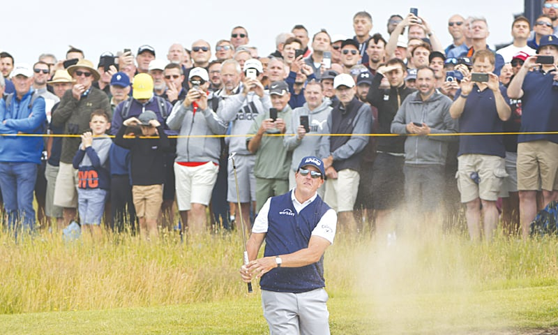 SANDWICH: Phil Mickelson of the US plays out of a bunker on the first hole during the second round of the British Open at Royal St George's on Friday.—AP