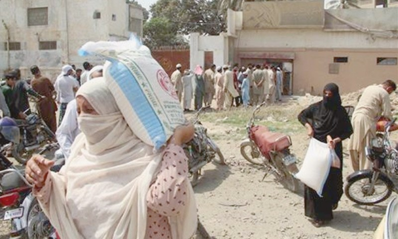 In this file photo, two women take away bags of flour while other people queue up for the essential commodity at a Korangi mill. — Online