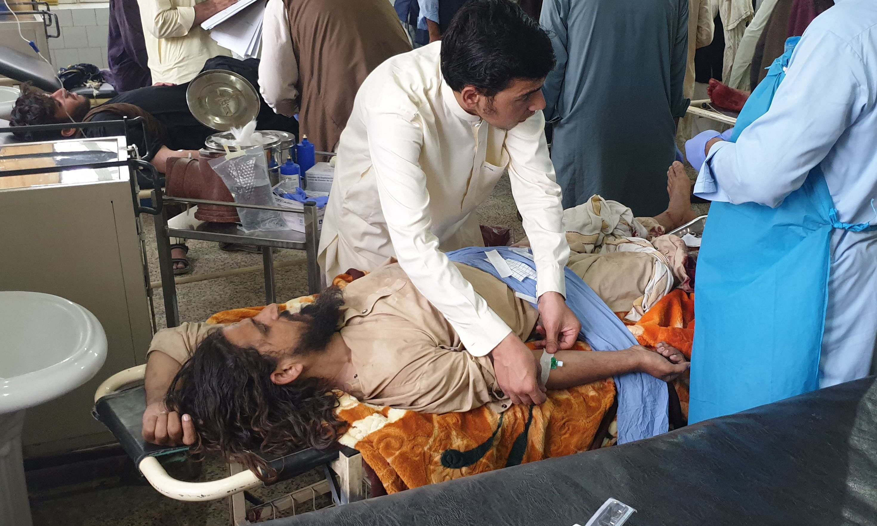 Paramedics treat men injured during fighting between Afghan forces and Taliban fighters, at a hospital in Chaman on Friday. — AFP
