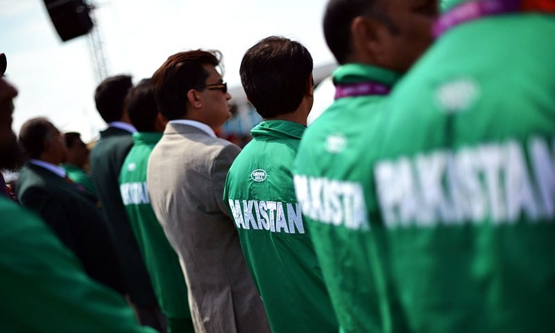 Pakistani athletes listen to the Olympic anthem during the flag raising ceremony held at the Olympic village in London in this file photo. — AFP/File