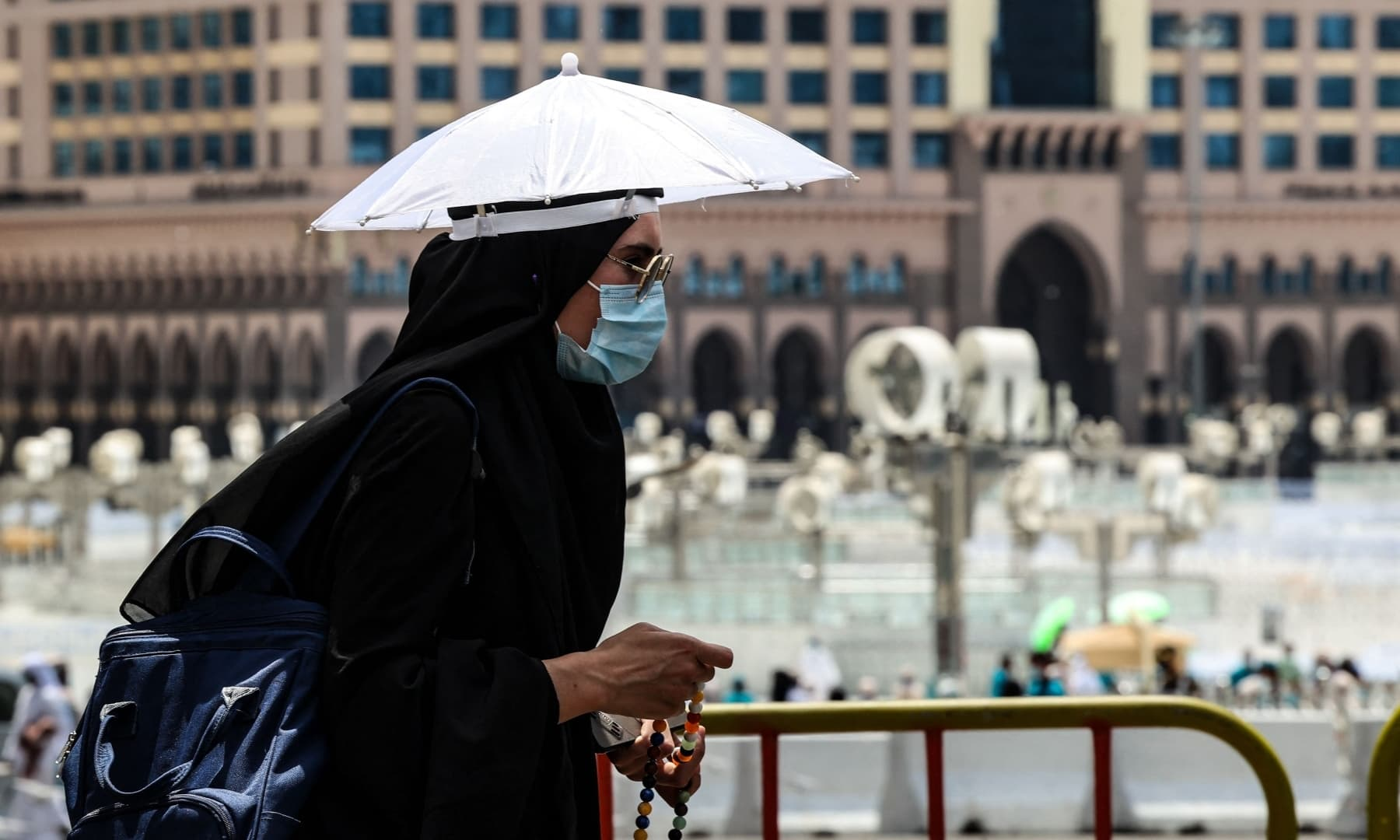 A pilgrim wears an umbrella hat to protect herself from the sun, in the holy city of Makkah, Saudi Arabia, July 16, 2021. — AFP