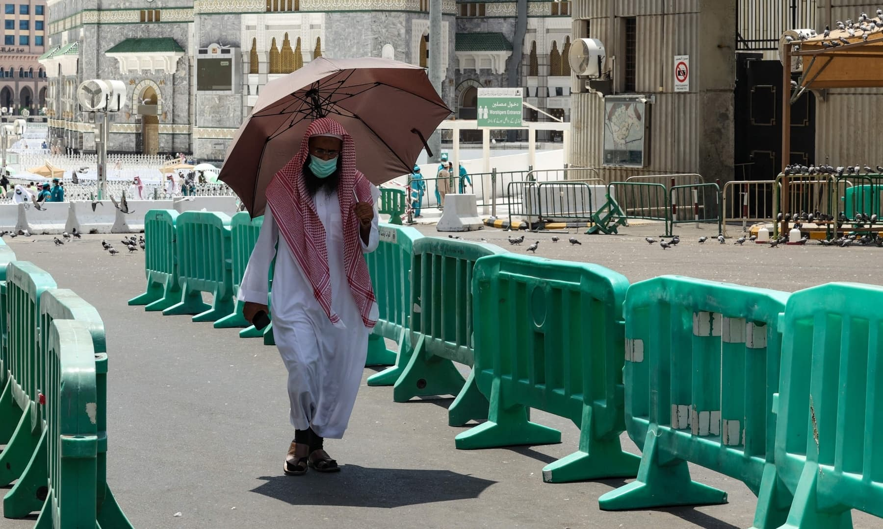 A pilgrim carries an umbrella to protect himself from the sun, in the holy city of Makkah, Saudi Arabia, July 16, 2021. — AFP