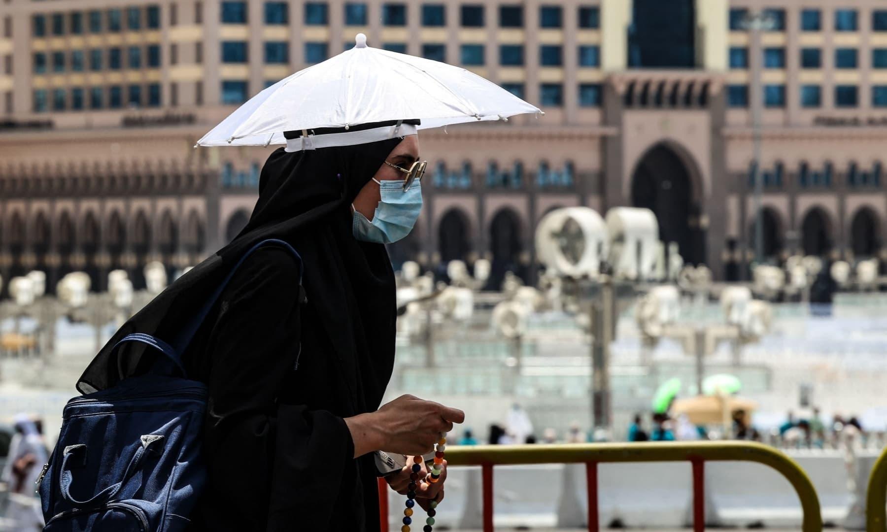 گرمی کی شدت سے بچنے کے لیے زائرین چھتریوں کا استعمال کر رہے ہیں - فوٹو:اے ایف پی