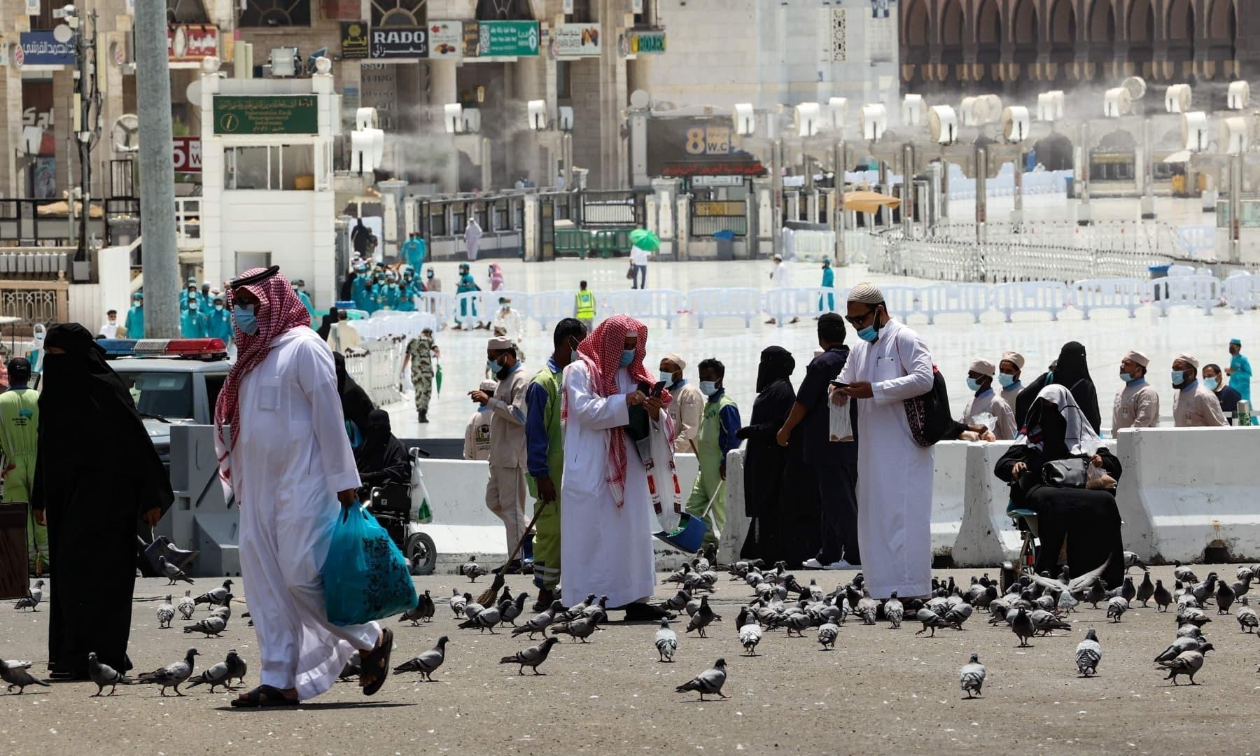 زائرین مسجد الحرام کے باہر کبوتروں کو کھانا ڈال رہے ہیں - فوٹو:اے ایف پی