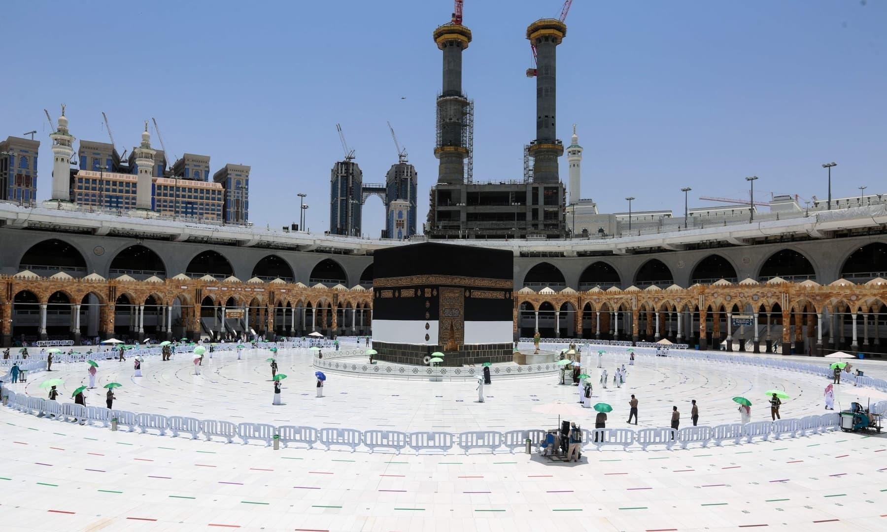 سعودی عرب کے مقدس شہر مکہ مکرمہ میں سعودی سیکیورٹی فورسز کا عملہ کعبہ کے گرد کام کر رہے ہیں- فوٹو:اے ایف پی