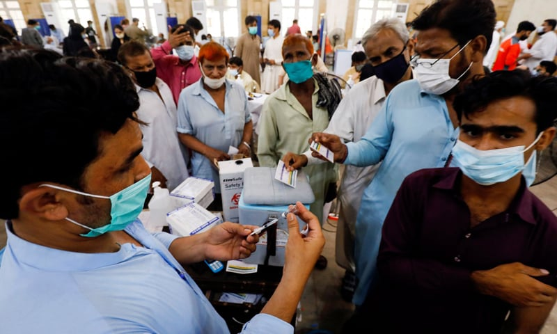 In this file photo, people gather to receive their Covid-19 vaccine doses at a vaccination center in Karachi, Pakistan. — Reuters/File