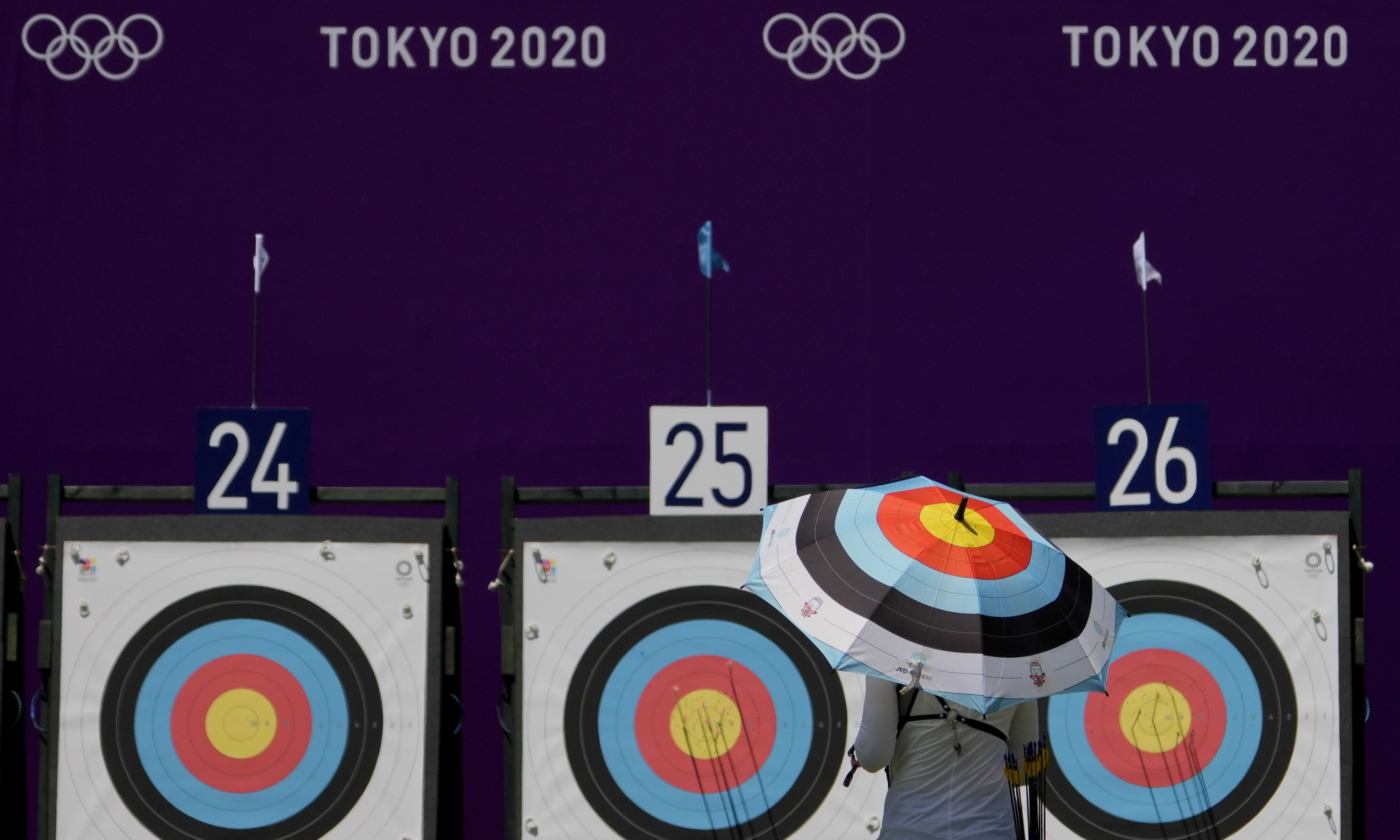 An athlete from Ukraine walks to collect her arrows as she practices for the 2020 Summer Olympics at Yumenoshima Park Archery Field, on Sunday, in Tokyo. — AP