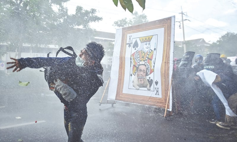 BANGKOK: A pro-democracy protester throws an object at police as others take cover from water cannon behind a derogatory image of Thailand's prime minister during a march on the Government House on Sunday.—AFP