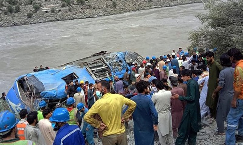 Rescue workers and onlookers gather around a bus after it plunged into a ravine in Dasu on July 14. — AFP/File