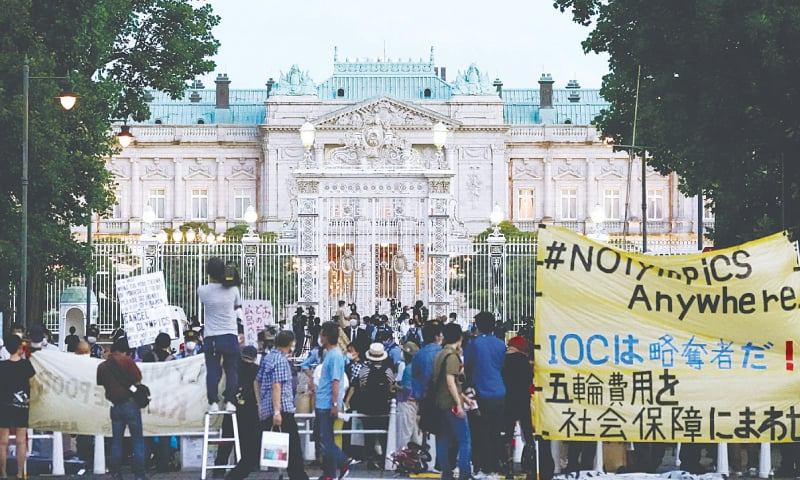 """Protesters against the Tokyo Olympics gather outside Akasaka Palace, Japanese state guest house, where the welcome party for IOC President Thomas Bach and its officials is held on Sunday. The banner, yellow, reads """"IOC is a looter ! Use Olympic fees for social welfare"""".—AP"""