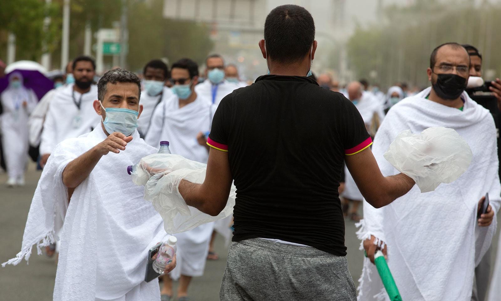 مسجد نمرہ آمد پر رضاکاروں نے عازمین میں پانی کی بوتلیں تقسیم کیں—فوٹو:اے پی