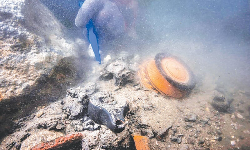 A DIVER unearths pieces of pottery in the sunken city of Thonis-Heracleion on Egypt's Mediterranean coast.—AFP
