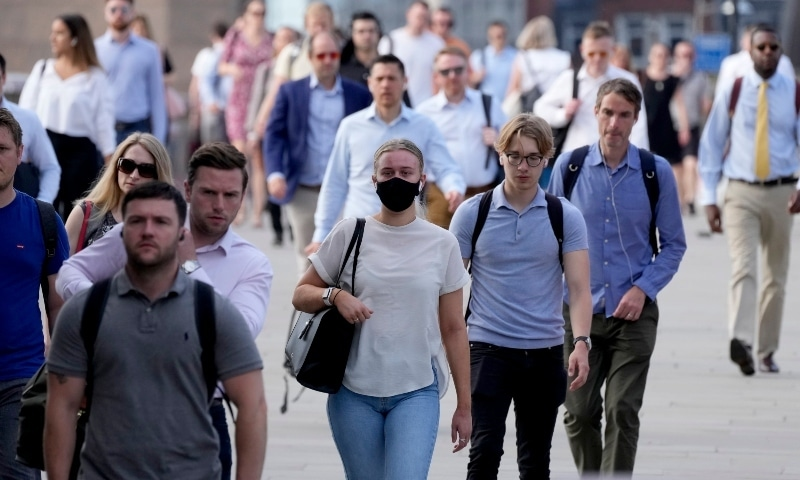 """On what has been dubbed """"Freedom Day"""", marking the end of coronavirus restrictions in England, some wearing masks people walk over London Bridge during the morning rush hour on July 19. — AP"""