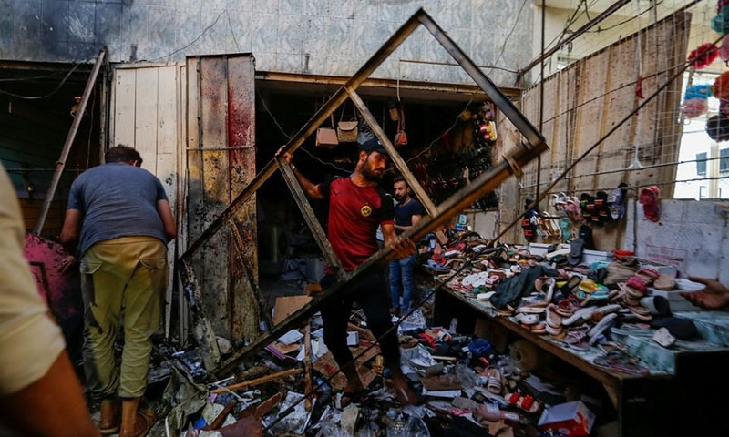 People pick up debris at the site of an explosion in Sadr City district of Baghdad, Iraq on July 19, 2021. — Reuters