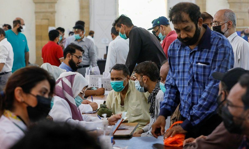 People wait to get vaccinated against Covid-19 at a centre in Karachi. — Reuters/File