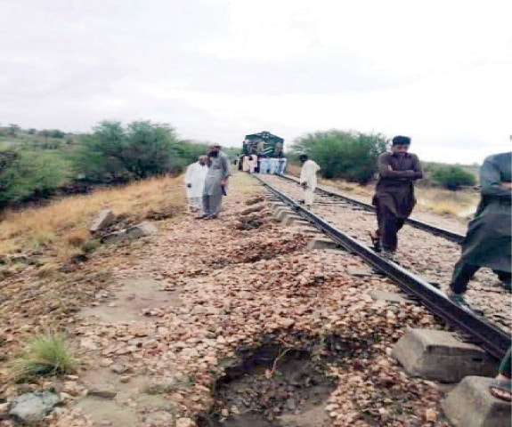 Passengers look at the damaged track on the Attock and Mari Indus route on Tuesday. — Dawn