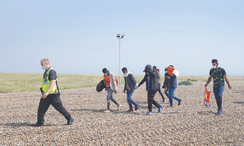 A POLICE officer escorts a group of people, thought to be migrants, from the beach in Dungeness, southern England,  on Tuesday.—AP