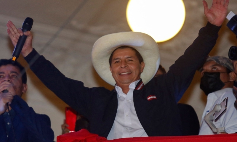 Leftist school teacher Pedro Castillo raises his arms from the balcony of the Peru Libre party headquarters in Lima, following the official proclamation of him as Peru's president-elect on July 19. — AFP