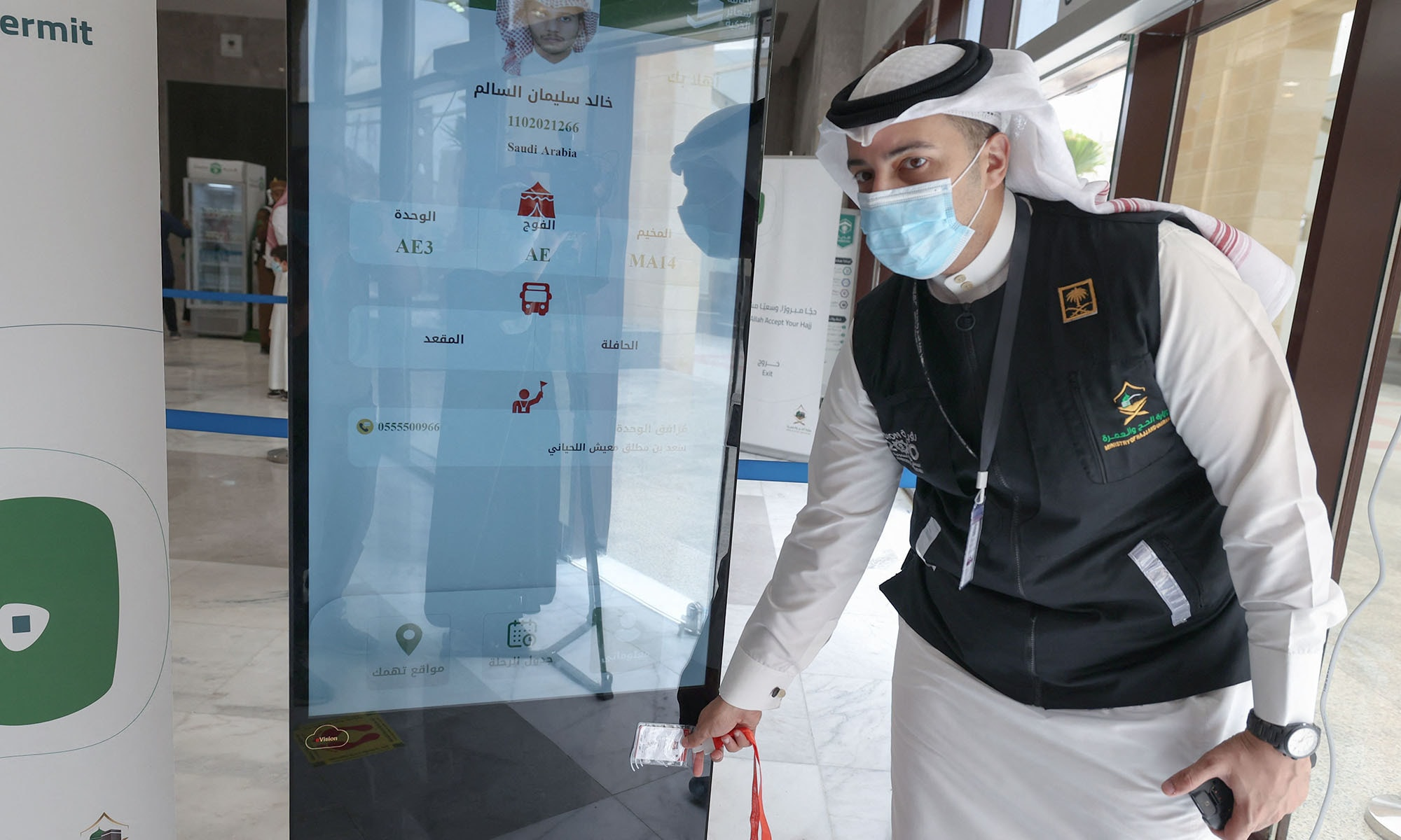 A Saudi member of staff scans a pilgrim's Haj card, allowing contactless access to religious sites, accommodation and transport, at a reception centre in Mecca on July 18, 2021. The plastic cards are available in green, red, yellow or blue, with the colour corresponding to markings on the ground guiding pilgrims through the different stages of Haj. Each card contains basic information about each pilgrim including their registration number, exact location of their accommodation, mobile phone number and the ID number of their guide. — AFP