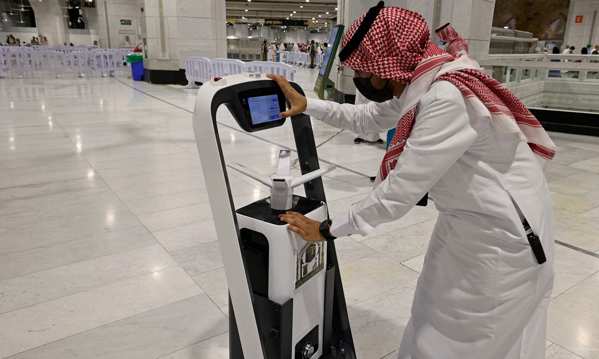 A Saudi staff works on a smart sterilising robot at the Grand Mosque in Saudi Arabia's holy city of Mecca, during the yearly Haj pilgrimage amid the Covid-19 pandemic on July 20, 2021. — AFP