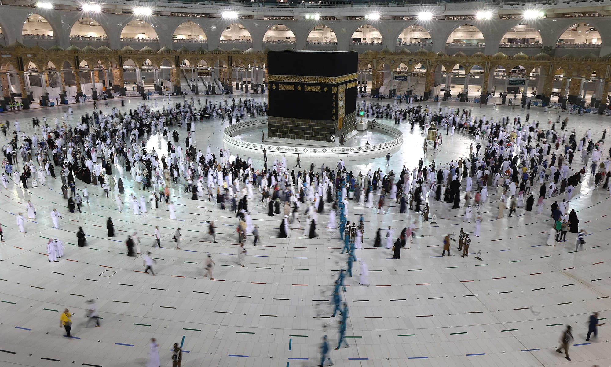"""Worshippers pray around the Kaaba, Islam's holiest shrine, at the Grand mosque in the holy Saudi city of Mecca, on the first day of the al-Adha feast celebrated by Muslims worldwide, on July 20, 2021. - The Eid al-Adha, or """"Feast of Sacrifice"""", marks the end of the annual pilgrimage or Hajj to the Saudi holy city of Mecca and is celebrated in remembrance of Abraham's readiness to sacrifice his son to God. (Photo by Fayez Nureldine / AFP)"""
