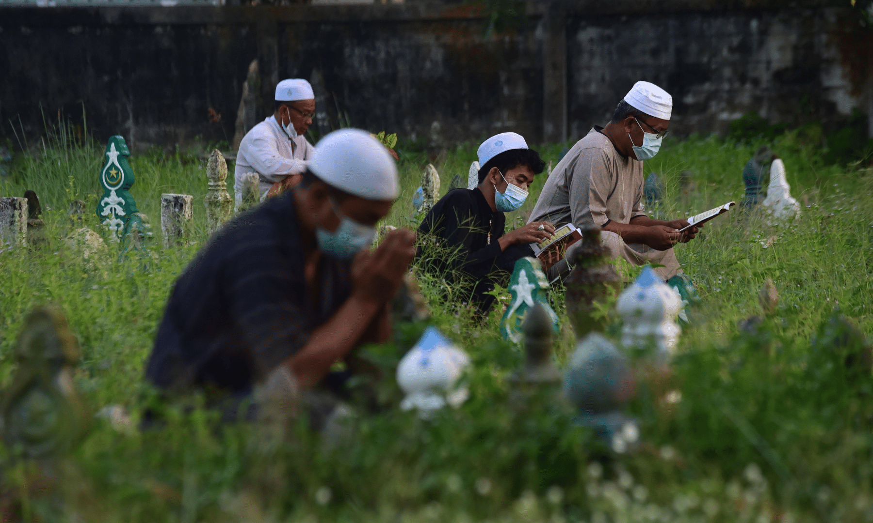 People pray next to the grave of relatives at a cemetery during Eidul Azha in Thailand's southern province of Narathiwat. — AFP