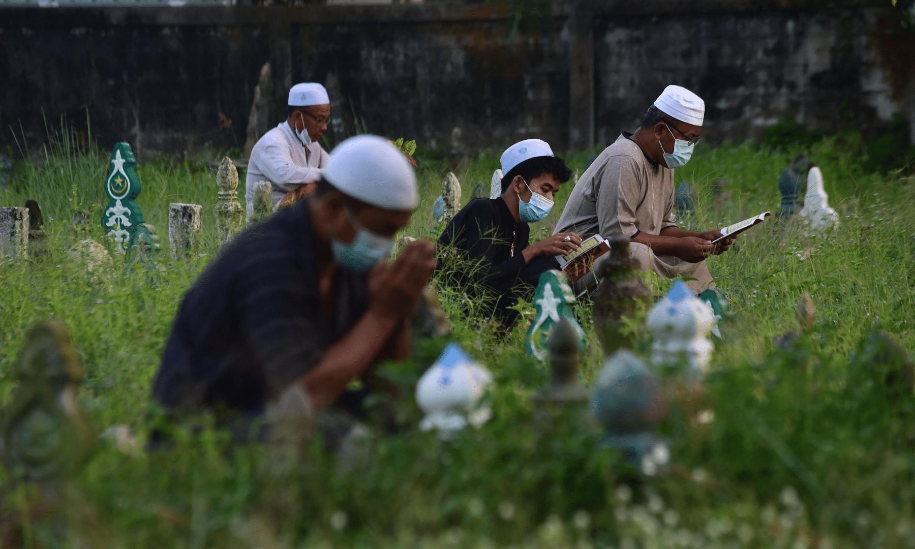 تھائی لینڈ میں عید کے اجتماع کی ادائیگی کے لوگوں اپنے پیاروں کی مغفرت کے لیے قبرستان میں فاتحہ خوانی کررہے ہیں— فوٹو: اے ایف پی