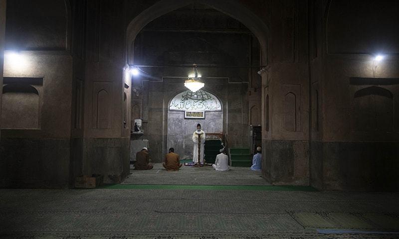 سری نگر کی مسجد کے امام پابندی کے سبب محض چند افراد کے سامنے عید کا خطبہ دے رہے ہیں— فوٹو: اے پی